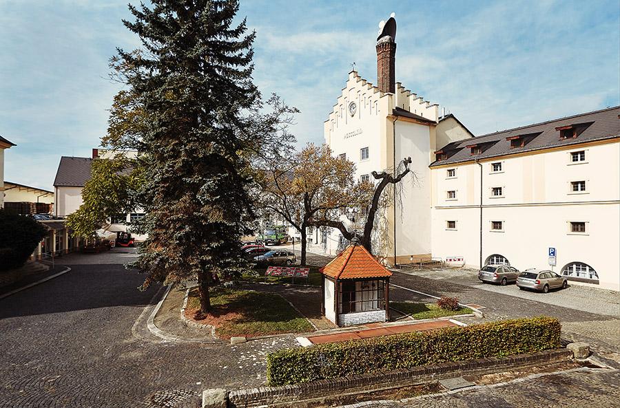 Pivovarský dvůr v Krušovicích s dominantnou historické varny a jejím komínem s tzv. kloboukem pana starého, plechovým nástavcem natáčejícím se podle směru větru, který bránil průniku deště do komína.