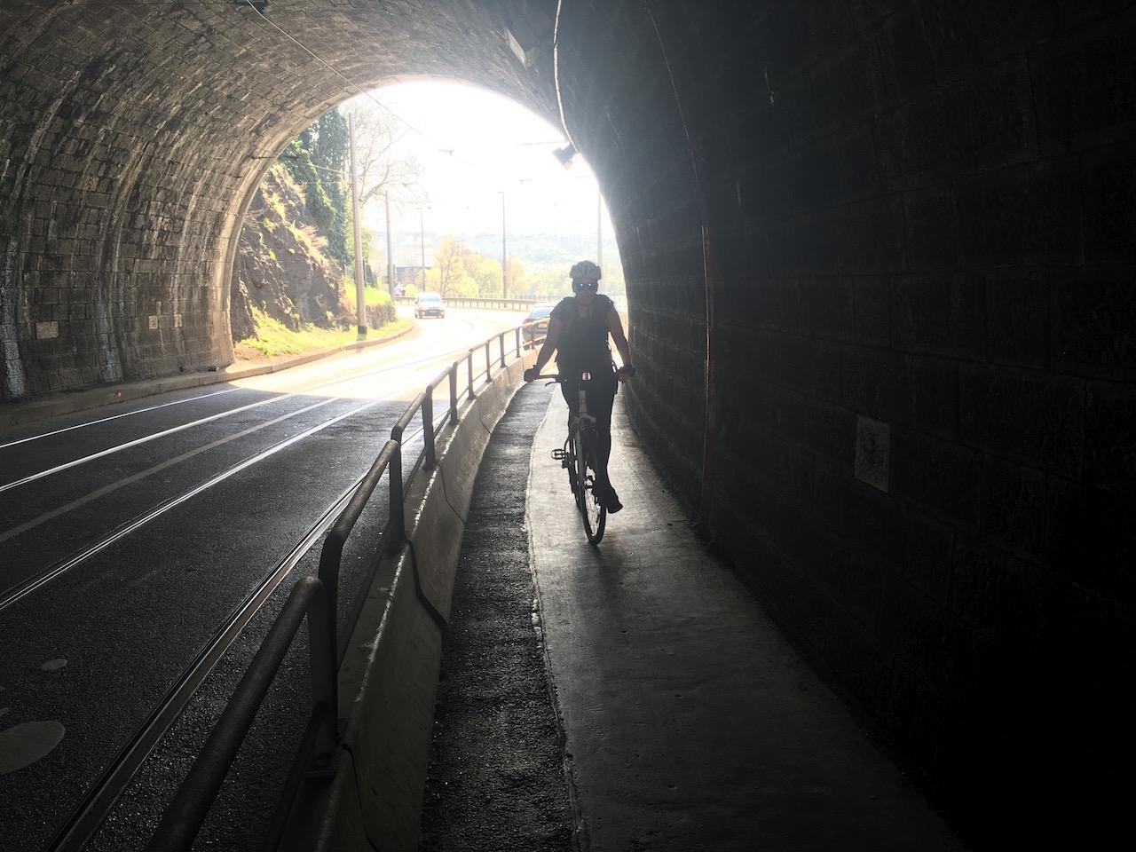 Cykloteroristka projíždějící přes zákaz Vyšehradským tunelem. Sestřelí prvního chodce za zatáčkou.