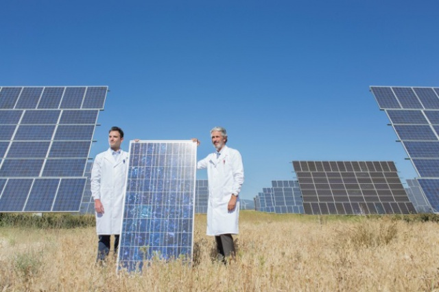 Scientists holding solar panel in rural landscape