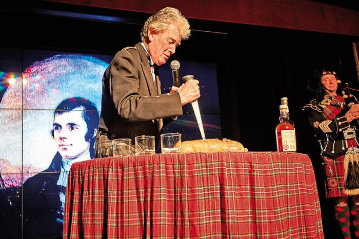 Ceremoniální rozříznutí haggisu se ujímají známé osobnosti – zde skotský moderátor Grant Stott.