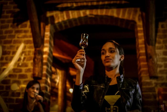 """'Rumová velvyslankyně' Anabel Hernández Gómez předvádí, jak si na vnitřních stranách sklenky vytvořit """"rumové nohy""""."""