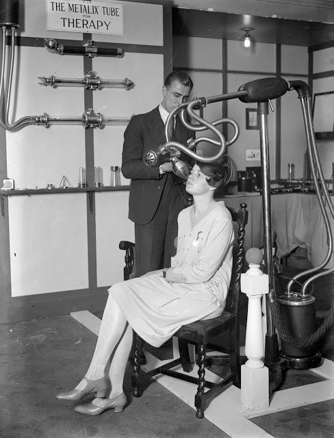 Muž se ženou demonstrují, jak funguje rentgenové zařízení. To představovalo zázrak moderního lékařství a léčení (1928)