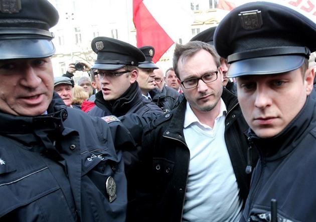 Antisemita a extremista Adam B. Bartoš putuje, kam patří - v poutech do policejní cely.