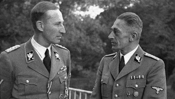 Dva Němci v hovoru, nebo Němec Heydrich rozmlouvá s Čechem Frankem, nebo říšský Němec hledí na českého Němce. Tři možnosti a všechny tři jsou správné.