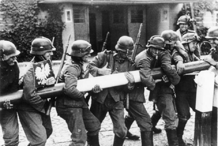 Němečtí vojáci nadšeně strhávají polskou hraniční závoru. Invaze do Polska a s ní i 2. světová válka začíná.