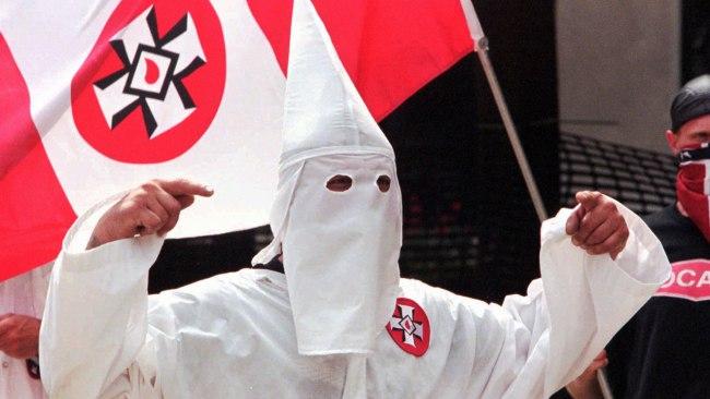 Člen KKK s vlajkou s logem Ku-klux-klanu