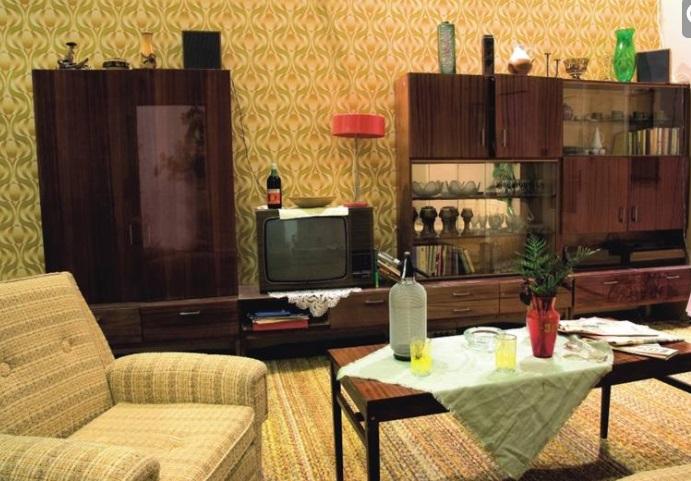 Obývák se sedací soupravou, stručně sedačkou, konferenčním stolkem, sifonovou lahví a typickými tapetami.