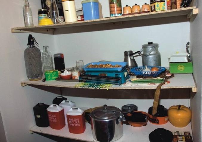 Kompletní prohlídka špajzu: vlevo nahoře univerzální lahev všech limonád a sodovek, pod ní vedle sifonové lahve skleněná litrovka od mléka vystřídaná později igelitovými pytlíky a aluminiový tlakový hrnec Kukta.