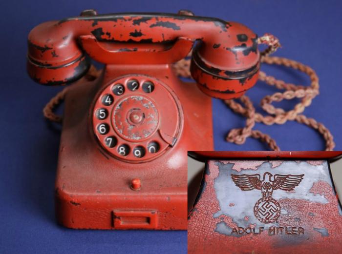 Hitlerův telefonní aparát s vyrytým hákovým křížem a jeho jménem.