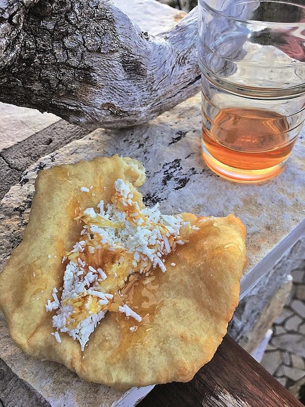 Nezvyklá chuťová kombinace: smažená placka, slaný sýr, med a sklenice sladkého vína.