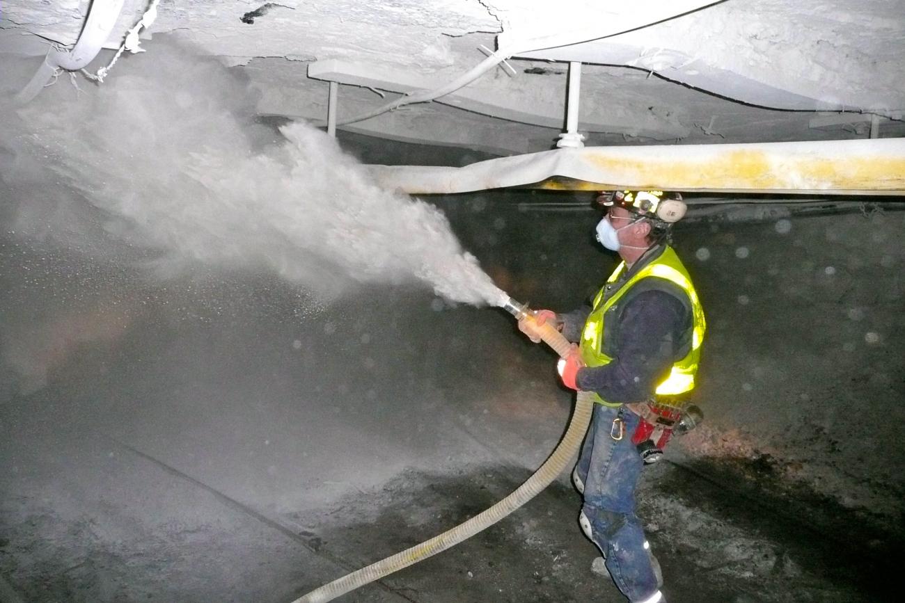 Horník stříká stěny mletým vápencem, aby preventivně zamezil vzniku nebezpečných koncentrací uhelného prachu