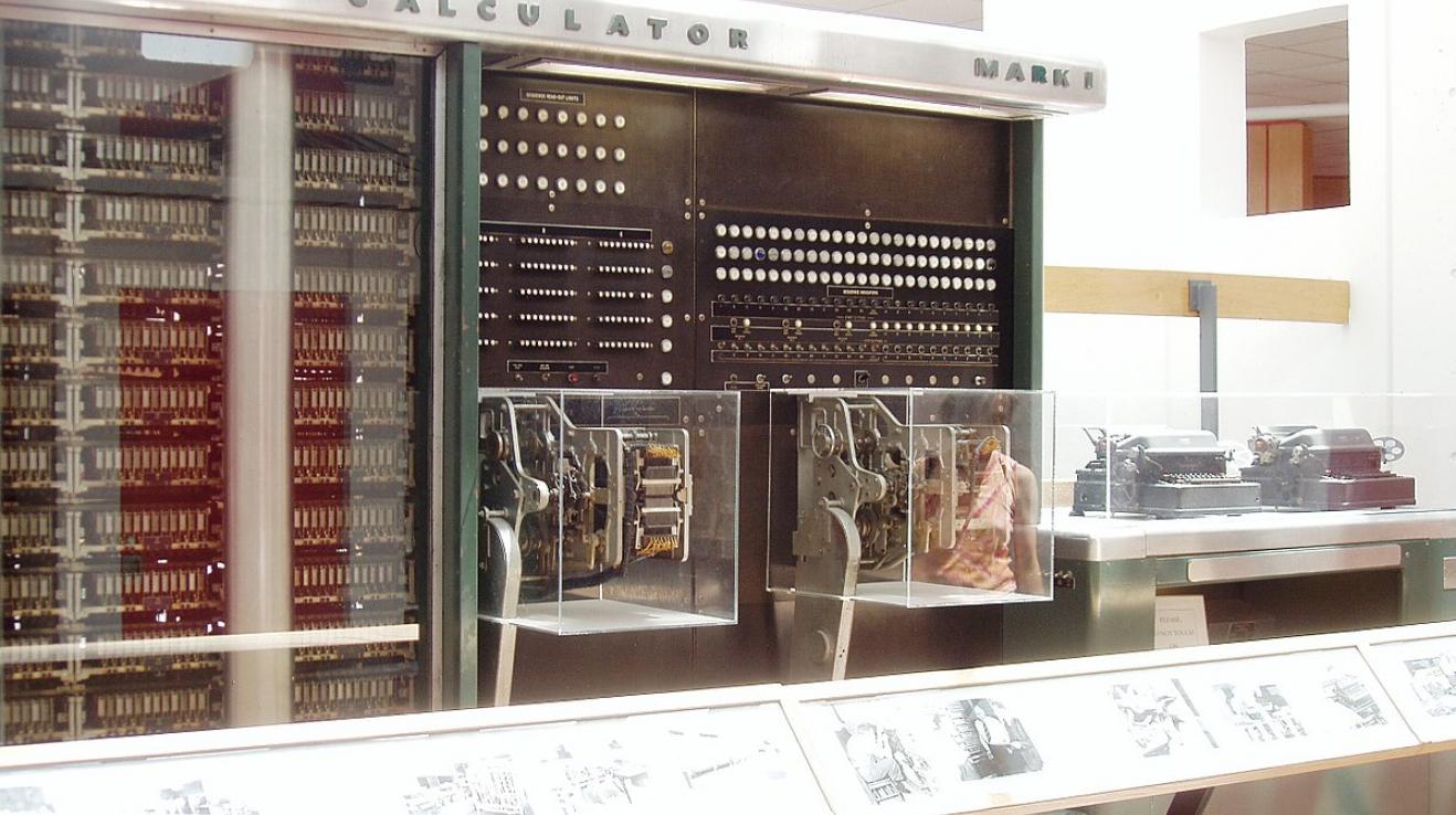 Mark I. nepřipomíná dnešní počítače ani vzdáleně. V pozadí jsou vidět výstupní zařízní - psací stroje.