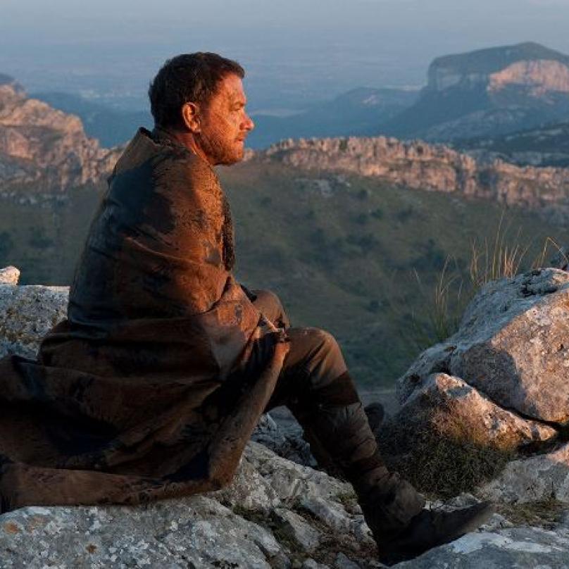Záběr z filmu Atlas mraků, ve kterém si Tom Hanks zahrál hned čtyři role. Lékaře, jaderného fyzika, gangstera a vesničana z postapokalyptické budoucnosti.