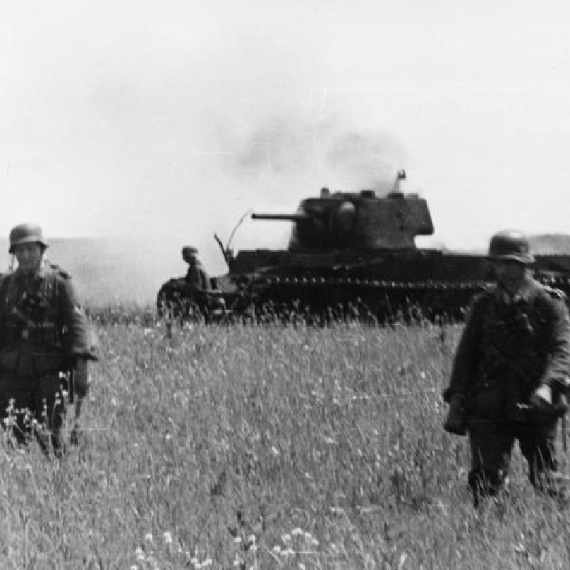 Postup německé pěchoty. Na pozadí zničený sovětský tank