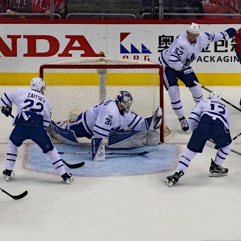 Banda chlapů na bruslích se s hokejkami honí za pukem