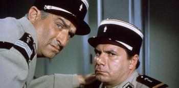 """Četník v New Yorku (1965) na snímku s ním velitel Michel Galabru. Velitel: Velitel: """"Cruchote! Jsem krajně nespokojen! Italové jsou už kompletní a vysmívají se nám! Já mám jednu absenci a dva šašky!"""""""