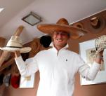 Na hlavě mexické sombrero, v pravé ruce kovbojský klobouk ze severního Mexika, v levé japonská baseballová čepičku z hadí kůže.